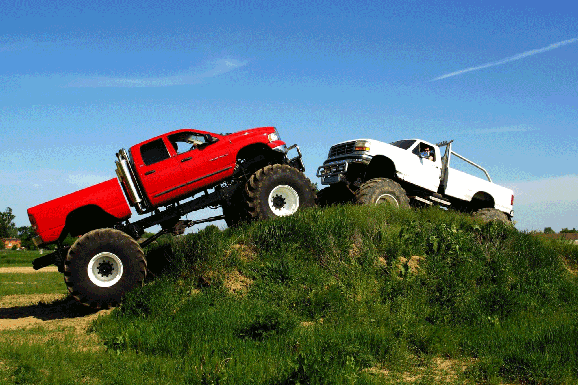 2 monster trucks facing each other on a hill