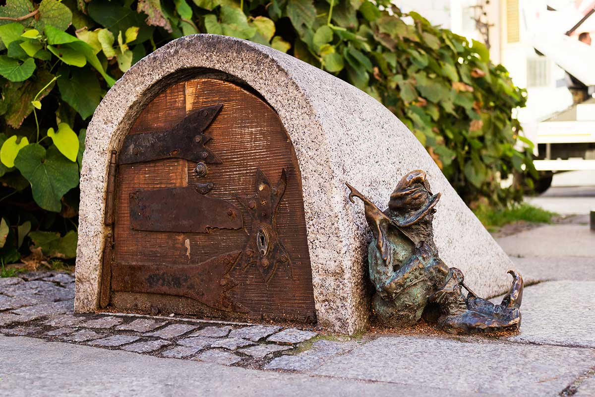 A dwarf, symbol of Wroclaw in Poland guards the entrance of a small building, sleeping next to the door